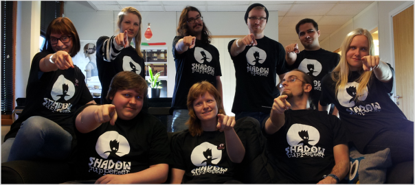 Shadow Puppeteer team in swag t-shirts pointing